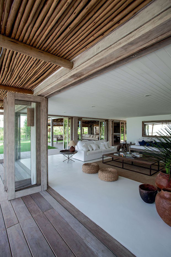 dream holiday home, scandinavia, brazil, beach house, dark rough wood, white resin flooring, lush green surroundings, rattan, terracotta, fold-away glass doors, summer, holidays, vacation, interior design, style, trend, natural, colour palette